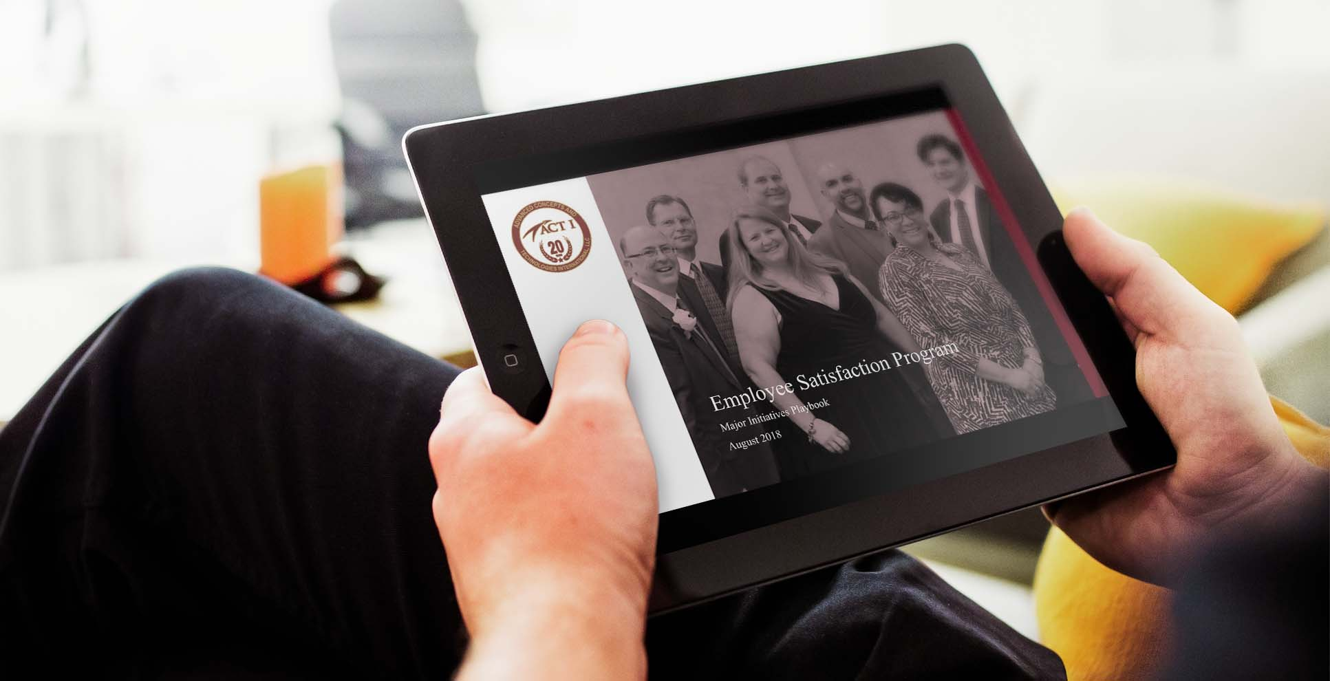 A person views an iPad with ACT I's Employee Satisfaction Program playbook on the screen